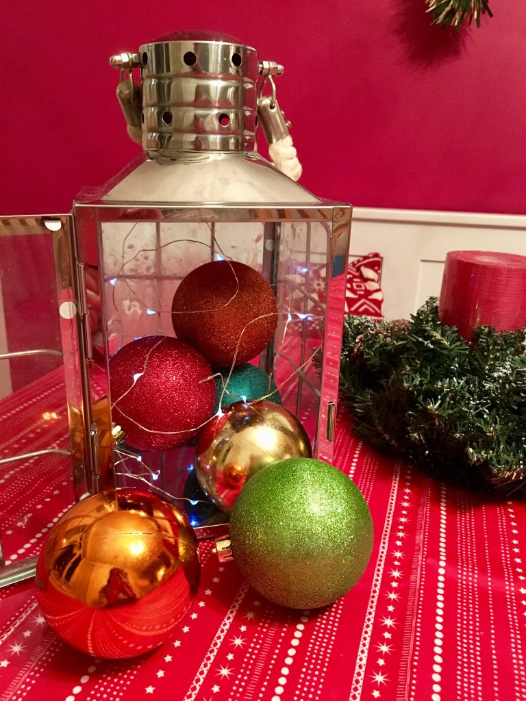Place baubles into the lantern while winding in the string lights.