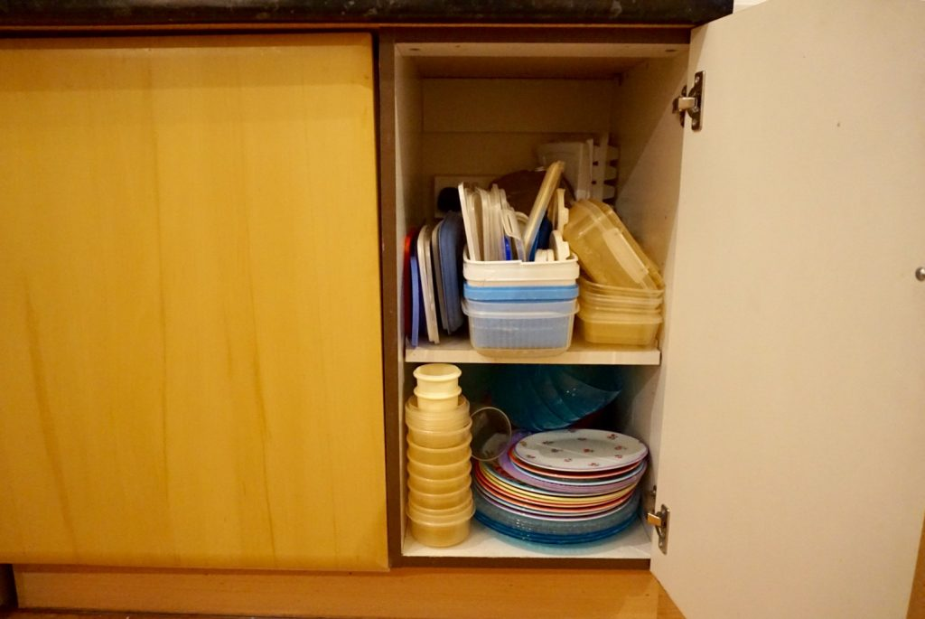Tupperware cupboard before being decluttered and organised