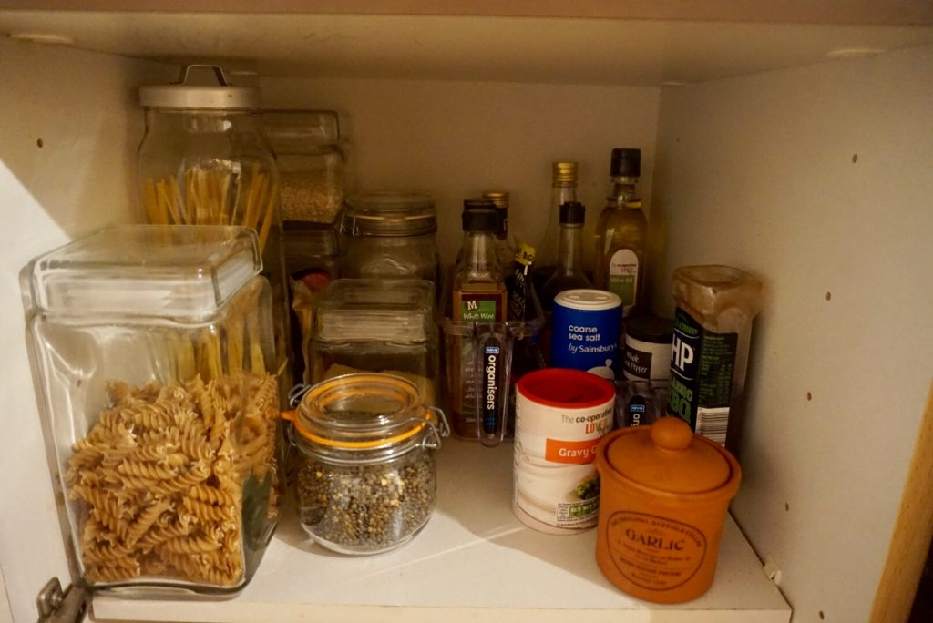 This shelf holds dry ingredients, oils and sauces