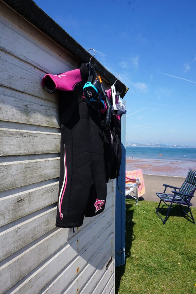 Beach hut with wetsuits hung up to dry