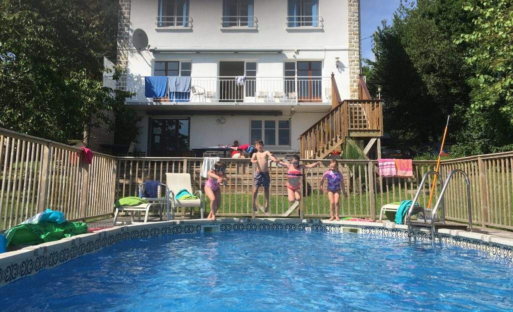 Looking back at the house with the kids jumping in the pool