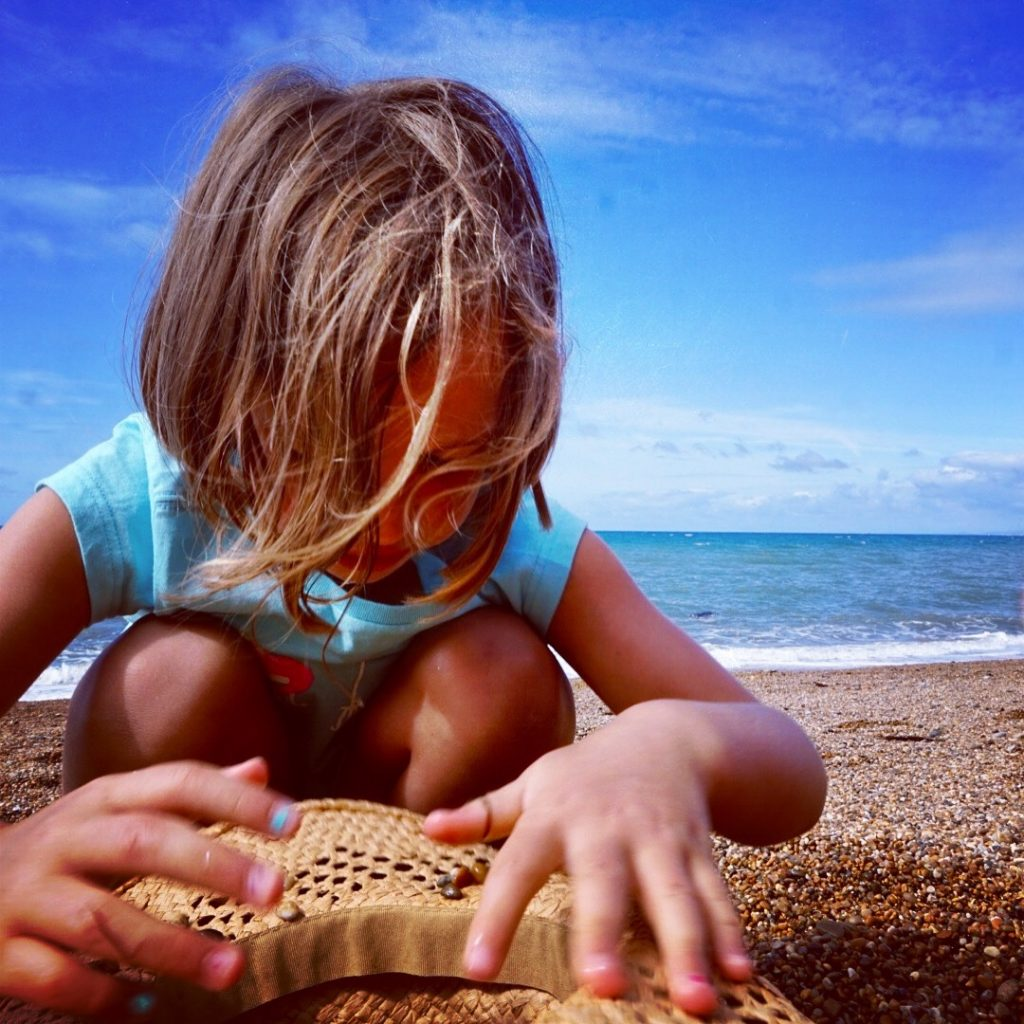 Little one playing with the stones on the beach