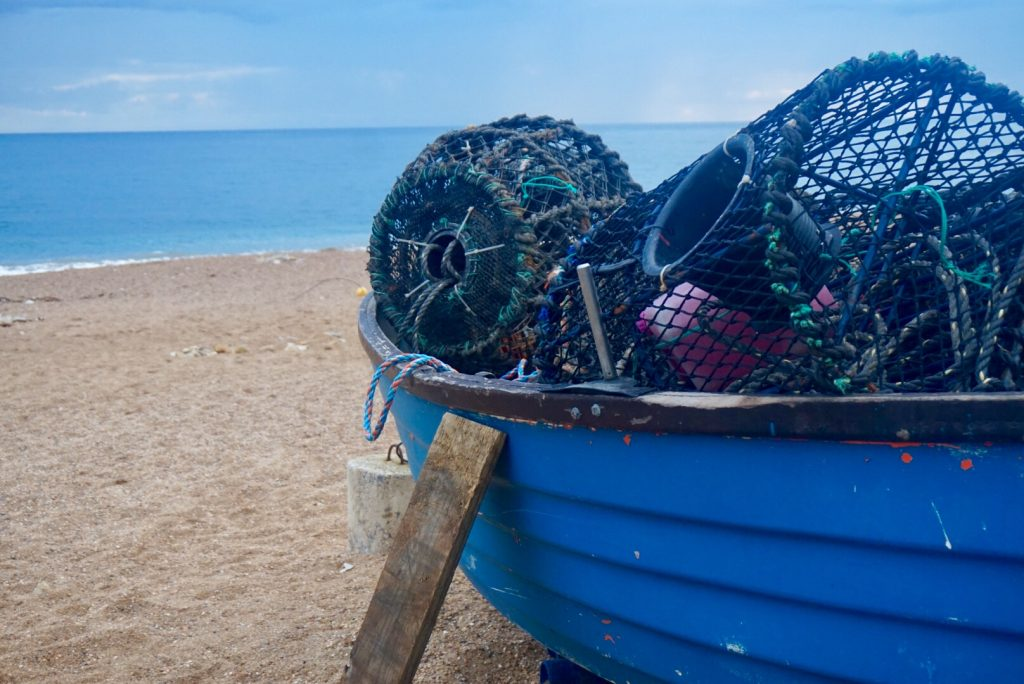 Boat full of lobster and crab pots at Hive Beach, Dorset