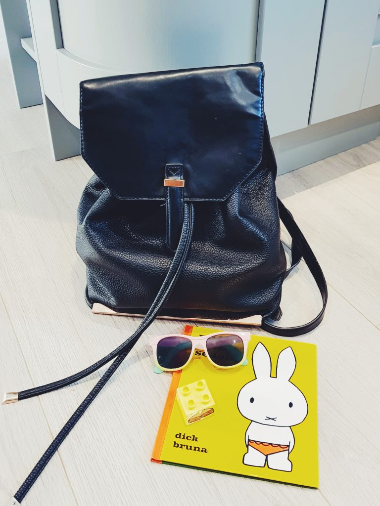 Black rucksack bag with sunglasses laid next to it
