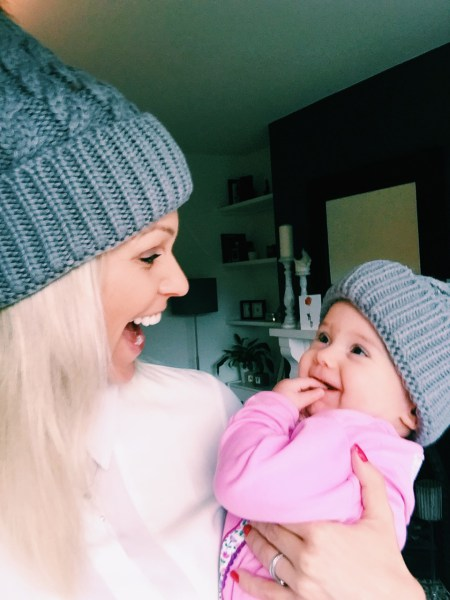 Emma Faith holding her daughter, they are both wearing grey hats