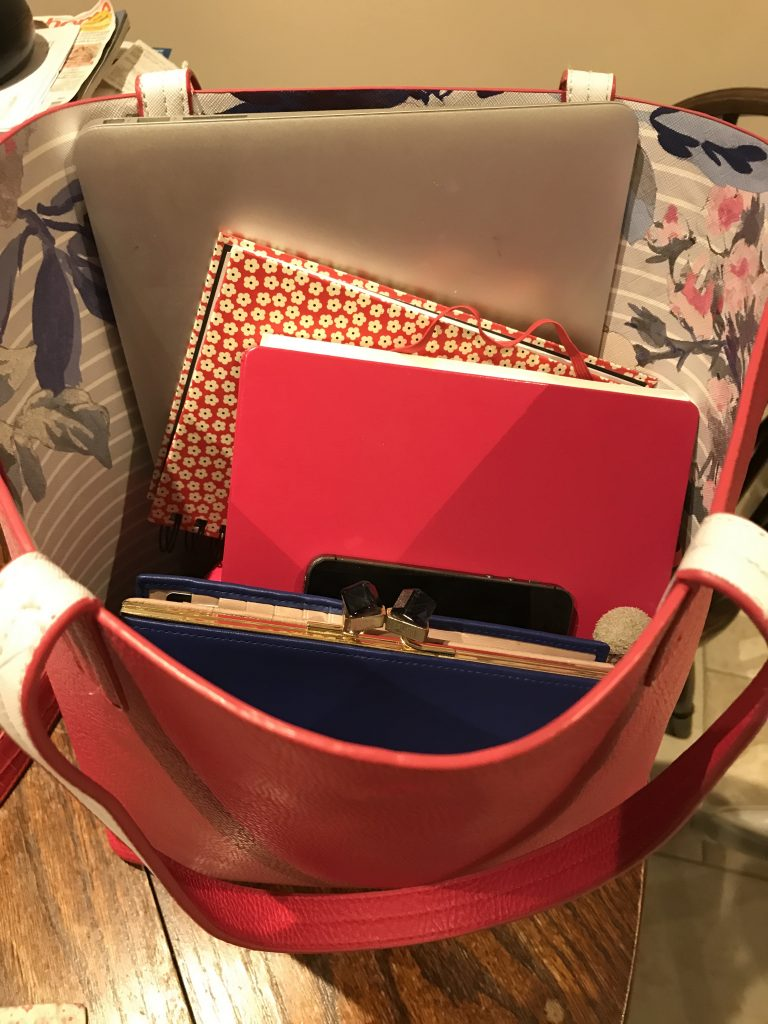 Red handbag which holds notebooks, laptop and purse
