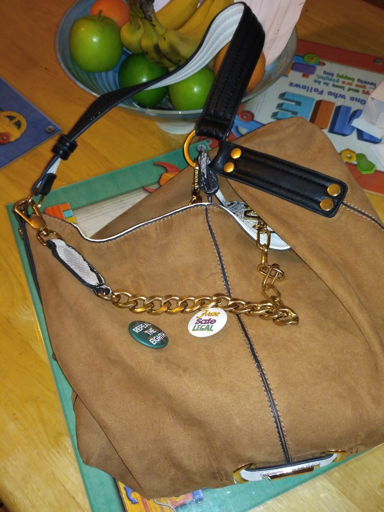 Tan hand bag with black strap on table