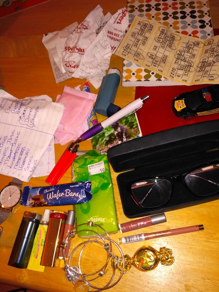 Content of Tracey's handbag including glasses, make up, inhaler and paper and pens